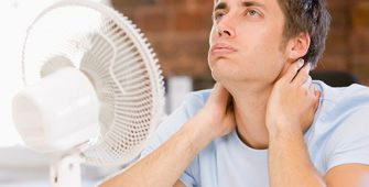man suffering in the heat with fan