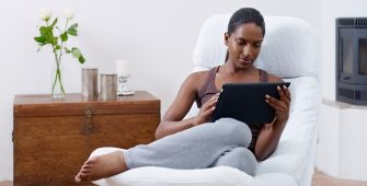 woman-relaxing-on-armchair-in-home-reading-online