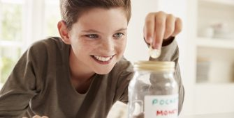 boy dropping coin into jar