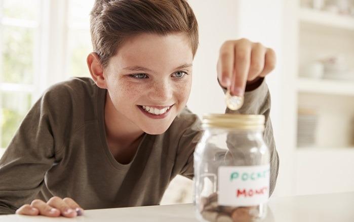 boy dropping coin into jar