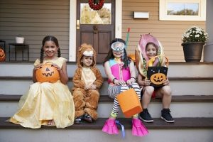 4 kids on a front porch in Halloween costumes